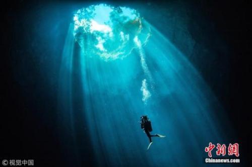 潜水员在一柱阳光中游泳。图片来源:视觉中国